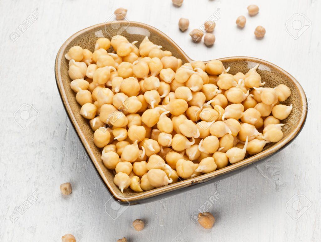 Chickpea sprout in heart shaped bowl on white wooden background